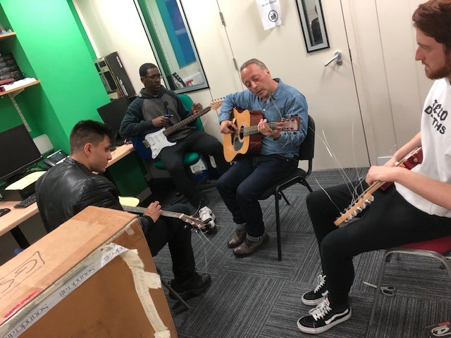 staff and students playing restrung guitars